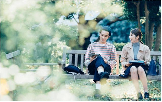 公園のベンチで談笑するカップルのイメージ写真