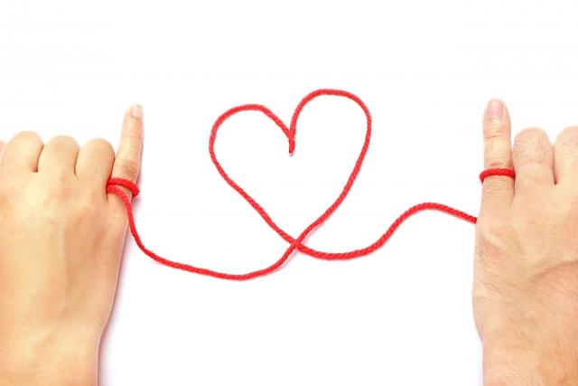 赤い糸で結ばれるカップルの小指の写真