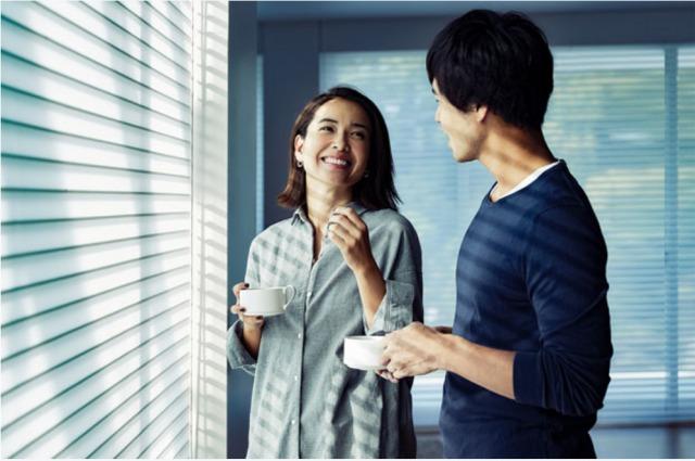 コーヒーを片手に談笑する男女のイメージ写真