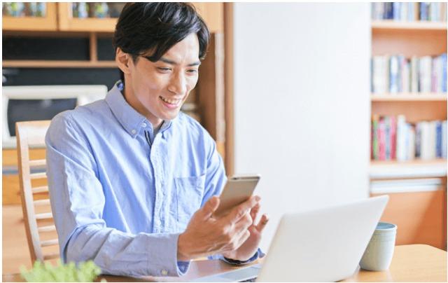 スマフォやパソコンで性格分析を受ける男性のイメージ写真