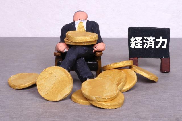 積まれたコインの前に座る男性の模型