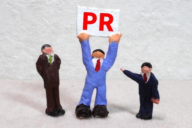 「PR」の看板を掲げる男性の模型