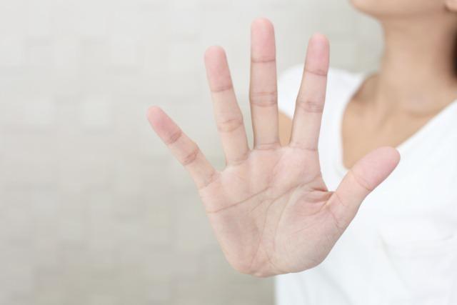 手を広げてストップサインを出す女性