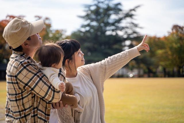 公園で何かを見上げる家族