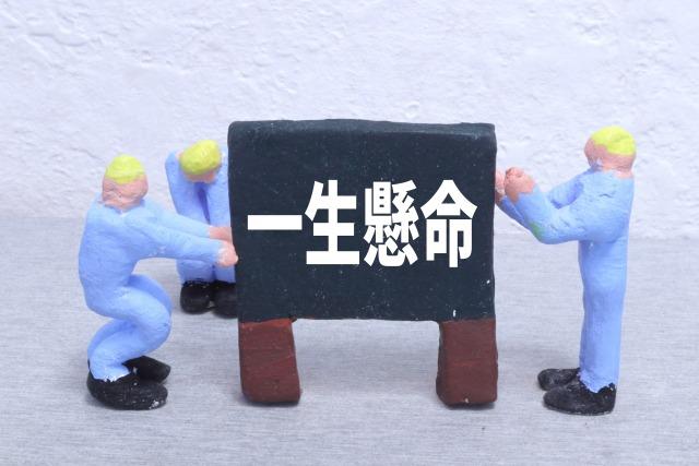 一生懸命と書かれたボードを支える人形