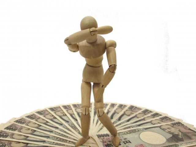 広げられた一万円札の上で泣く人形