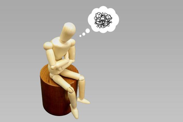 腕組みして考える人形