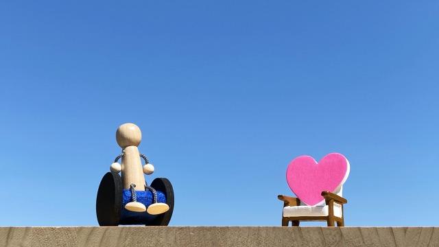 椅子に座る男性の人形と隣の椅子に置かれたピンクのハート