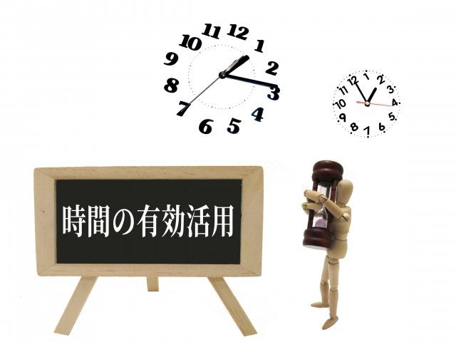 「時間の有効活用」と書かれたボードの傍で砂時計を持つ人形